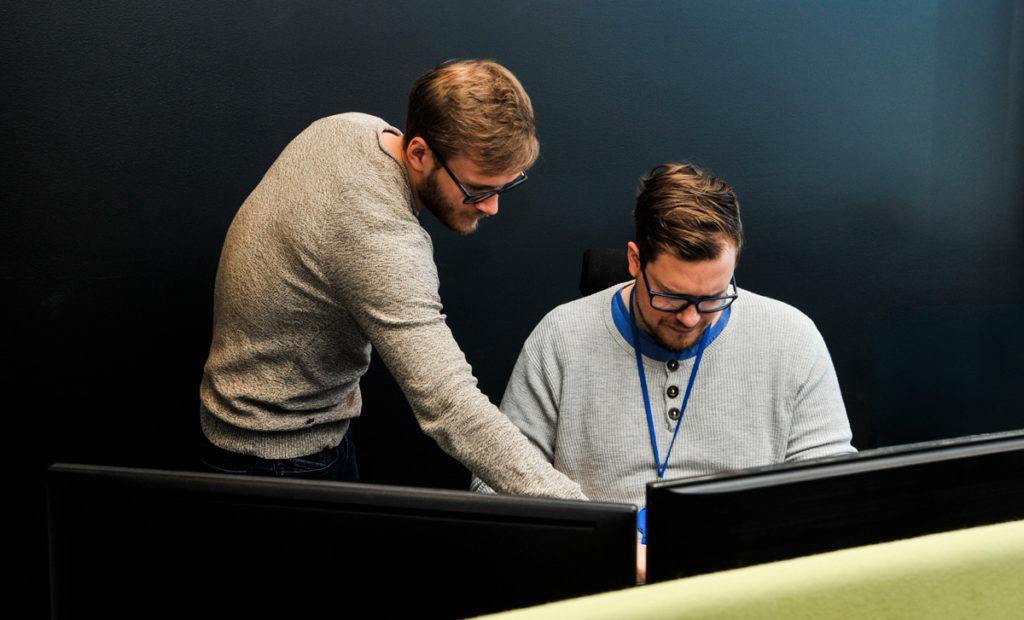 To supportmedarbeidere jobber sammen for å løse en sak i servicedesken